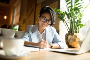 Cheerful asian lady filing profit tax return form in cafe